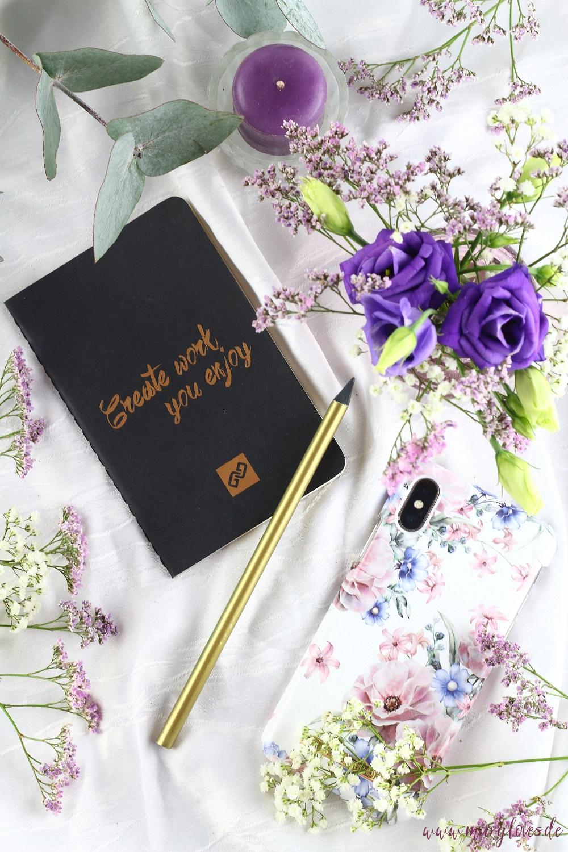 """Bild zum Thema Hallo 2020 - Blog-Vorsätze mit Notizheft """"Create work you enjoy""""mit Bleistift, Kerze und Blumenarrangement"""