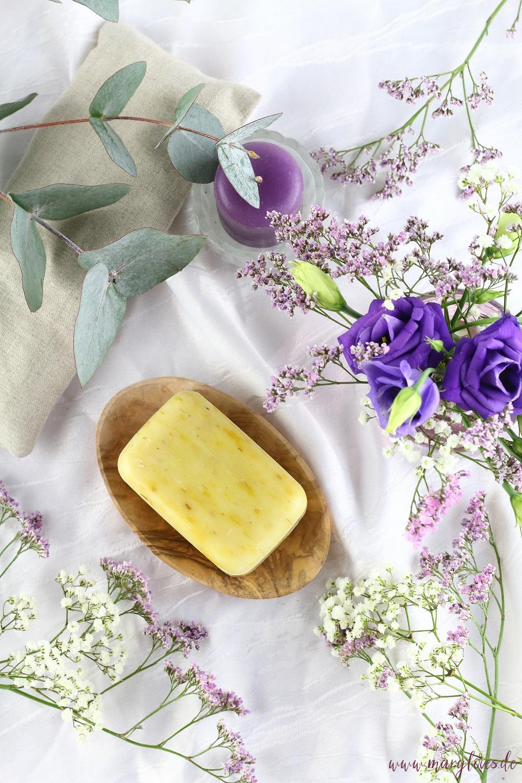 Naturkosmetik Naturseife arrangiert auf Olivenholz-Seifenschale zwischen Blumen