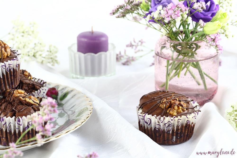 Walnuss-Schoko-Muffins mit Ahornsirup arrangiert auf gedeckter Kaffeetafel mit Blumen