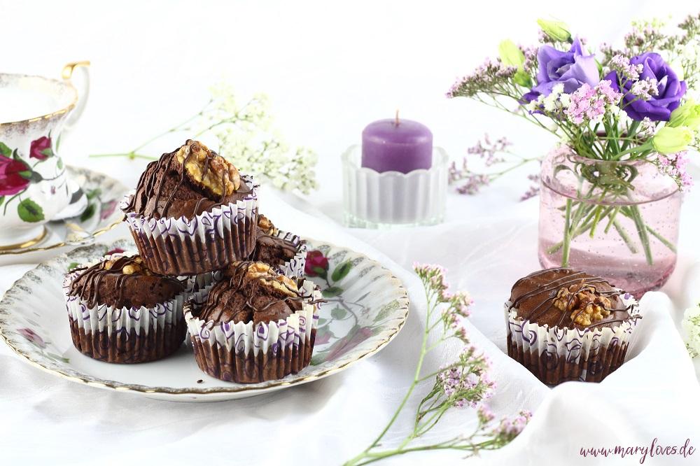 Walnuss-Schoko-Muffins mit Ahornsirup arrangiert auf gedeckter Kaffeetafel mit Blumen und einer Tasse Milchkaffee